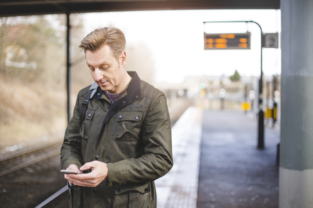 Man at a train station using his smartphone while he waits for his train.