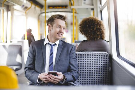 public transport: Formal businessman sitting on the train. He is holding a smartphone and looking out the window. Stock Photo