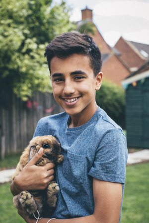 rabbit standing: Teenage boy standing in his garden with his rabbit in his arms. He is smiling at the camera.