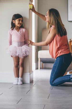 그녀의 어머니에 의해 그녀의 높이 측정 발레 의상 어린 소녀. 그녀는 어머니가 테이프를 사용하는 동안 벽에 서 있습니다.