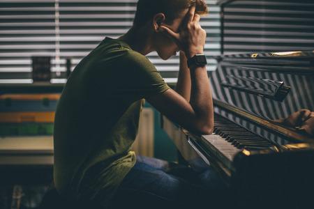 Adolescente che si siede al suo pianoforte con la testa fra le mani. Archivio Fotografico
