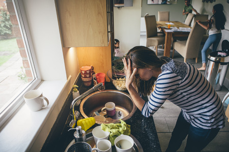 sibling rivalry: Stressed mum at home. She has her head in her hands at a messy kitchen sink and her children are running round in the background.