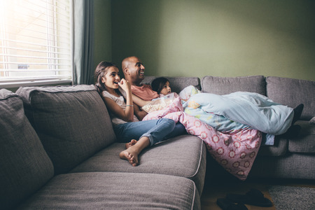 they are watching: Father curled up on the sofa with his two daughters. They are watching a movie with popcorn.