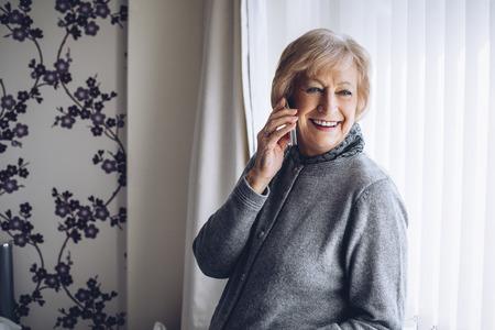 Senior vrouw lachend aan de telefoon in haar huis. Ze zit in haar slaapkamer en kijkt uit het raam. Stockfoto