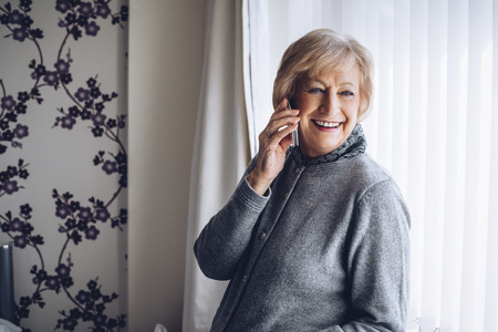 one senior woman only: Senior woman laughing on the phone in her home. She is in her bedroom, looking out the window. Stock Photo