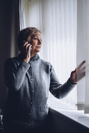 red handed: Senior woman talking on the phone whilst looking out of her window.