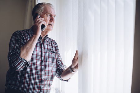 Senior man talking on the phone whilst looking out of his window. He has a worried look on his face.