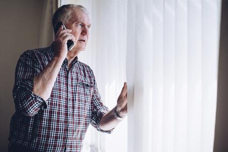 Senior man praten over de telefoon terwijl hij uit zijn raam kijkt. Hij heeft een bezorgde blik op zijn gezicht.