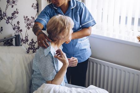 vistiendose: Asistente del hogar ayudar a una mujer mayor se visten en su dormitorio. Foto de archivo