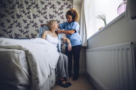 Thuisverzorgster helpt een oudere vrouw zich in haar slaapkamer aan te kleden. Stockfoto
