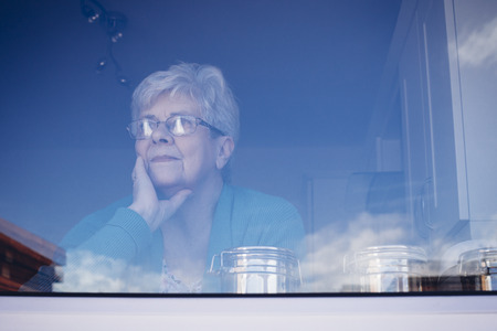 looking out: Senior woman looking out her kitchen window, deep in thought.
