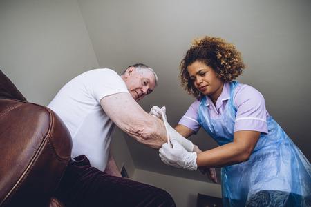 Caregiving Verpleegkundige zetten een pleister op een senior mans arm in zijn huis. Stockfoto