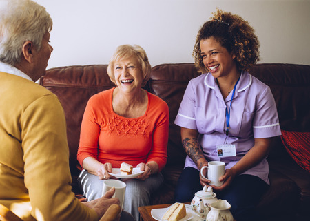Elderly carer sitting with two of her patients in the care home. They are enjoying some cake and tea. Stock Photo