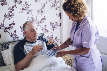 Bedbound senior man receiving assistance from a home caregiver. He is taking some medication with water.