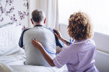Domácí pečovatelská sestra kontroluje starší muže plic s stetoskopem na zádech.