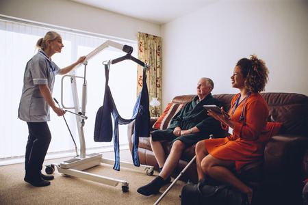 Two homecare nurses at an elderly mans house. They have a hoist set up.