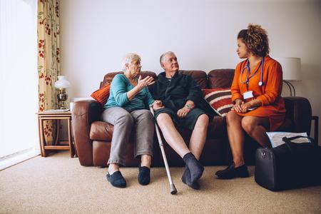 Coppia di anziani a parlare con il loro operatore sanitario a casa. Sono sittig sul divano in salotto.