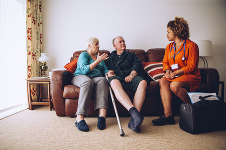health care worker: Elderly couple talking to their healthcare worker at home. They are sittig on the sofa in the living room.