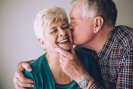 cheek to cheek: Senior man kissing his wife on the cheek. She has her eyes clsoed and is laughing.