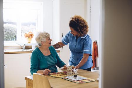 Hulpverlener geven van een oude dame haar diner in haar huis. Stockfoto