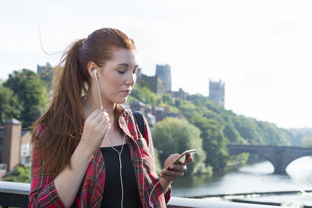 pulled over: A happy young woman smiles as she looks down at her phone  listening to her music by the river. She has her hair pulled back into a ponytail with her bag over her shoulder.