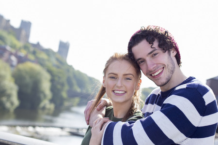 A happy young couple smile as they relax outdoors by the river. They are in an embrace.