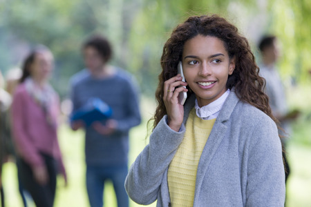 smiing: A happy young student smiles as she uses her mobile phone outdoors. She is wrapped up in a thick coat. A group of students are out of focus in the background.