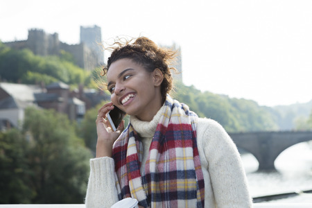 smiing: A happy young woman smiles as she uses her mobile phone outdoors. She is wrapped up warm for the winter and laughing as she looks off camera. Stock Photo