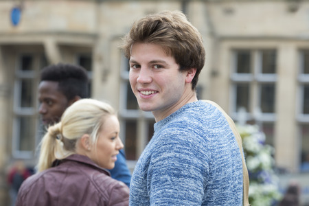 he: A happy student turns to smile at the camera as he makes his way to his lessons. He is carrying his bag over his shoulder and his friends are in the background out of focus. Stock Photo