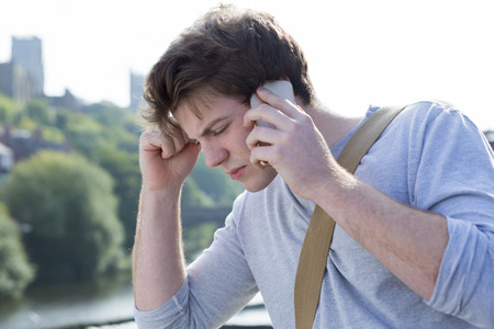A sad male student holds his head in his hands as he uses his mobile phone. He is getting bad news. A cathederal ca be seen in the background.