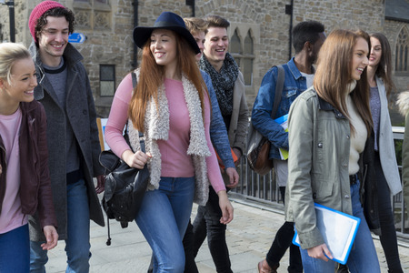 multi age: A group of happy young students smile as they walk through the city together on a break from university. They are carrying their bags, books and digital tablets. Stock Photo