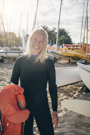 wetsuit: Portrait of a senior woman standing in a boat bay. She is wearing a wetsuit and holding a lifejacket.