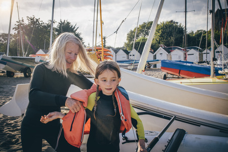 lifejacket: Little girl receiving a helping hand from her grandmother to get her lifejacket on. Stock Photo