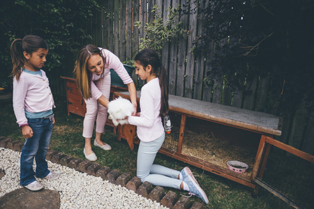 females only: Two sisters in the garden with their mother. They are holding their white pet rabbit.