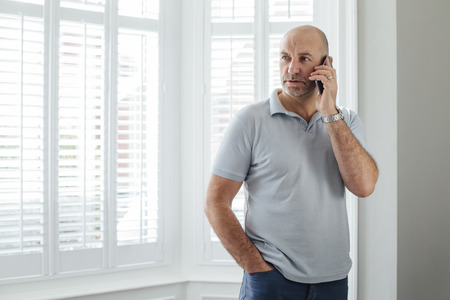 one mature man only: Man talking on the phone. He is standing by the window in his home with a serious expression.