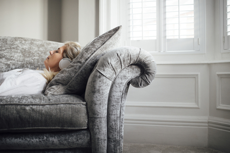 Mature woman lying on her sofa, enjoying listening to some music through headphones. Banque d'images