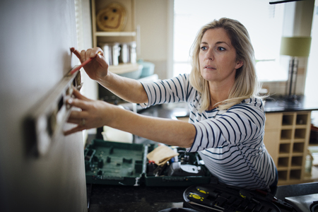 spirit level: Mature woman using a spirit level and marking the wall with a pencil in her kitchen. Stock Photo