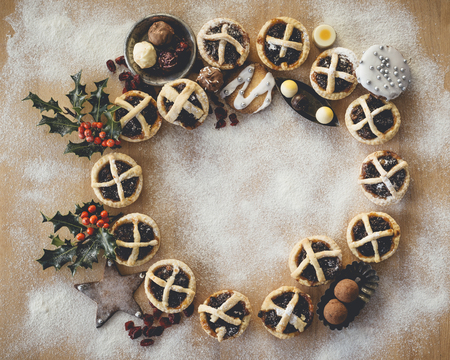 Mince Pies presented in a circle shape on a wooden chopping board.