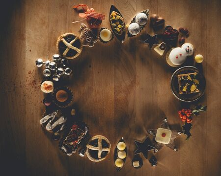 organised: Christmas treats and accessories presented in a circle on a wooden chopping board.  Stock Photo