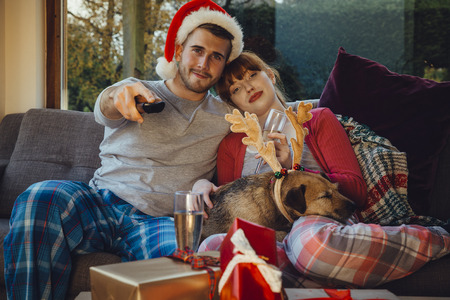 Young couple at home with their pet dog at Christmas time. They are all cuddled up on the sofa at home, watching television.