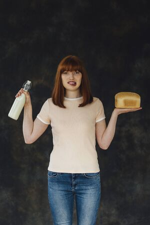 lactose intolerant: Woman standing against a studio background with a glass of milk and a loaf of bread in each hand. Stock Photo