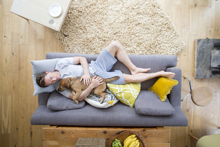 Man is lying on the sofa in the living room of his home. He has his dog lying on him who is also asleep. Фото со стока