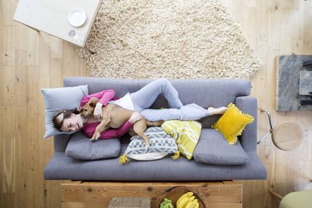 Young woman is lying on the sofa in the living room of her home with her pet dog. The dog is trying to lick it's owner, who is laughing and avoiding the dog.  Stockfoto