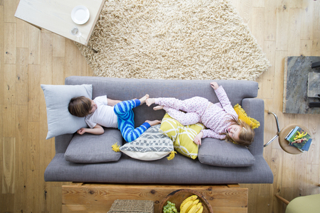 Children are sitting at opposite ends of a sofa in the living room of their home. They are wearing pyjamas and are playing around together.
