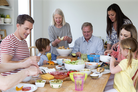 large family: Large family are sat round a table in the dining room of a home. They are eating mediterranean style food.