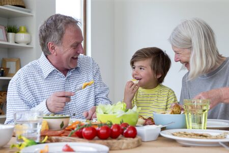 only senior adults: Little boy is eating lunch with his grandparents. They are enjoying a mediterranean style platter.