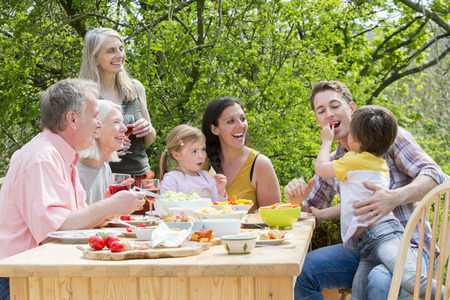 Three generation family having a garden party in the summer. Everyone is laughing and looking at the little boy, who is feeding his father some red pepper. Standard-Bild