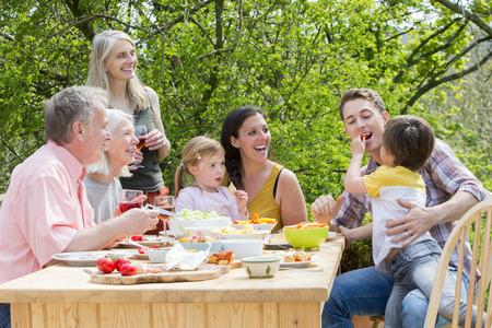 Tři generace rodiny se zahradní party v létě. Všichni se smějí a dívají se na malého chlapce, který krmí svého otce nějakou červenou paprikou. Reklamní fotografie