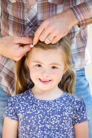 hairclip: Little girl is smiling for the camera while her father styles her hair with hairclips.