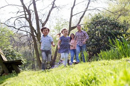 Un petit garçon et sa soeur courent dans l'herbe dans un parc naturel. Leurs parents ne sont pas au point et marchent derrière eux. Banque d'images